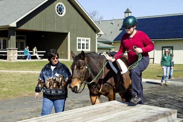 Barbara Finazzo, a volunteer with Special People United to Ride, or SPUR, leads Avery to the mounting block for Teddy Dieterman, a seventh-grader at Collier Middle School, to ride. / Mike McLaughlin/Asbury Park Press